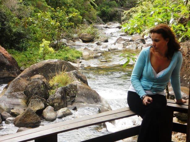 Mulher sentada na beira doRio de Visconde de Mauá cortando a pousada