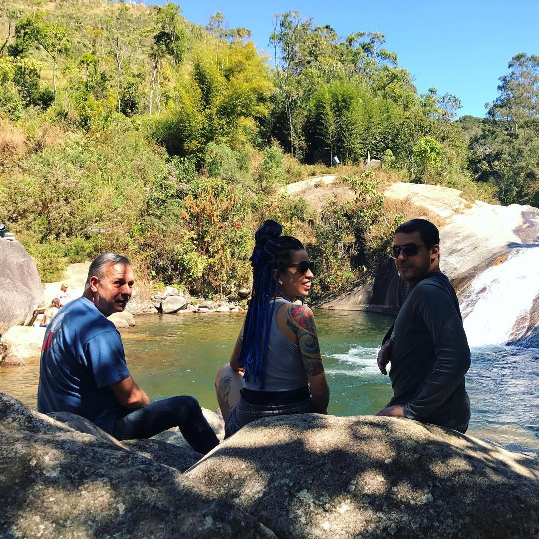 Três pessoas com o p[e na cachoeira