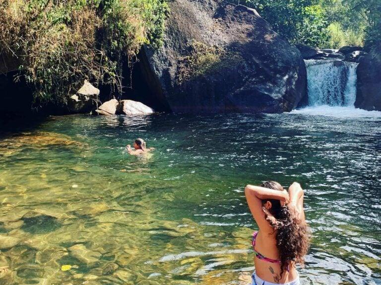 Moça se espreguiçando na cachoeira de Visconde de Mauá