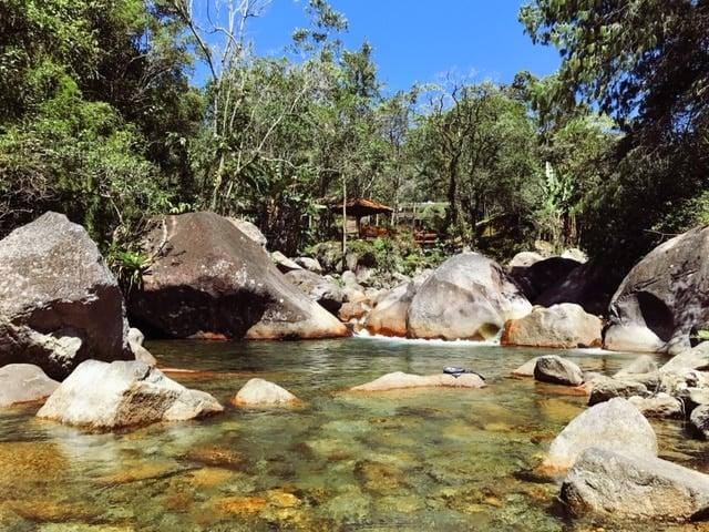 Rio de águas cristalinas descendo entre pedras