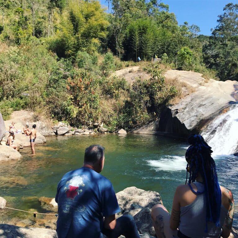 Casal de costas sentados na beira do rio comtemplando a cachoeira do Escorrega