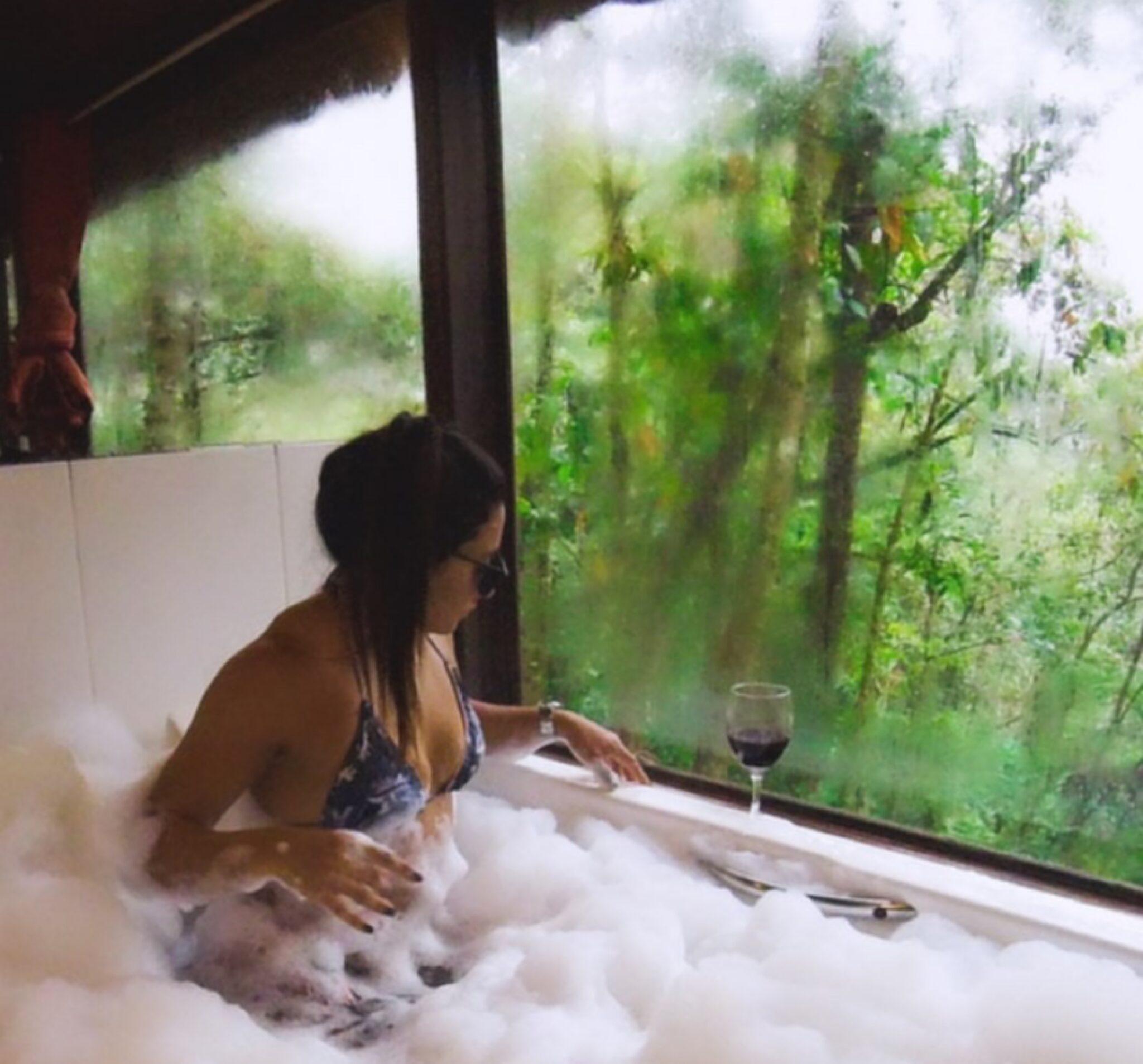 Moça dentro da banheira de biquíni, tomando vinho ao lado de uma janela ampla com vista da mata de Visconde de Mauá