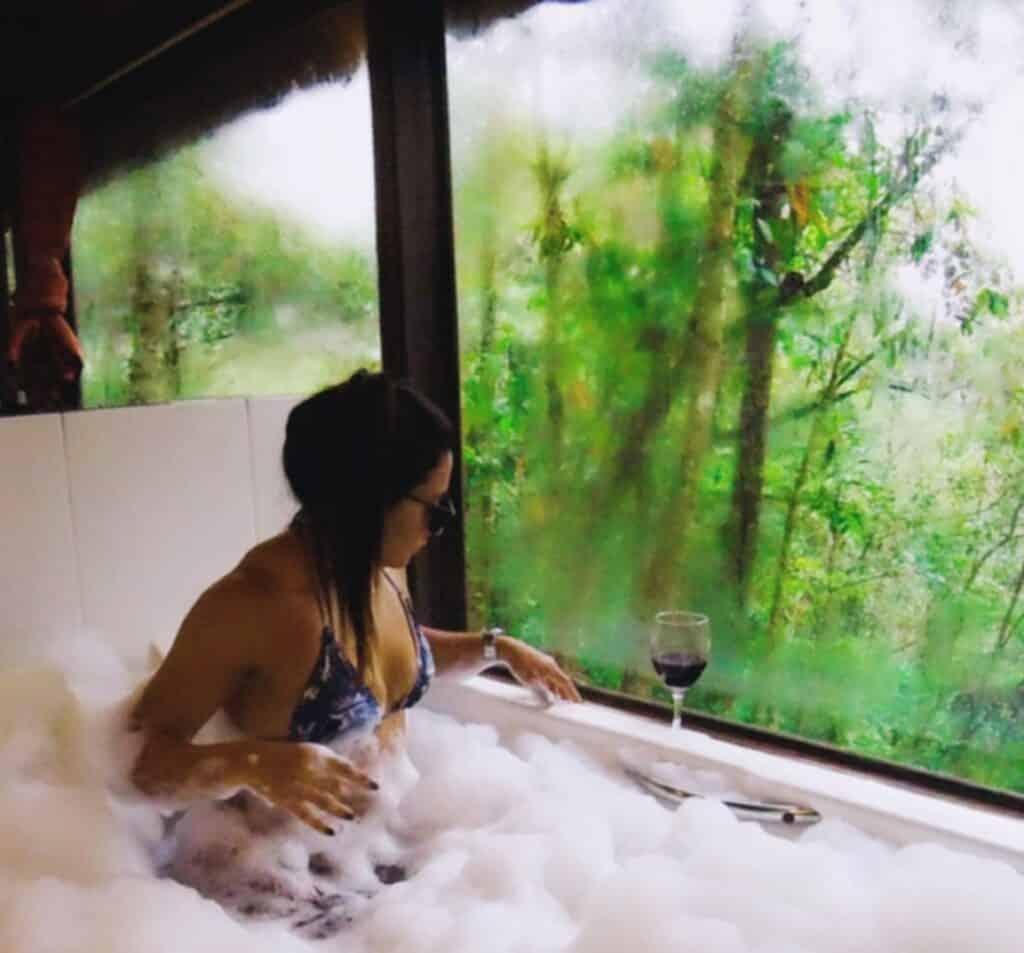Mulher tomando se banhando na banheira de biquini