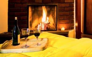 Lareira acessa com mesa ao lado com vinho e taças