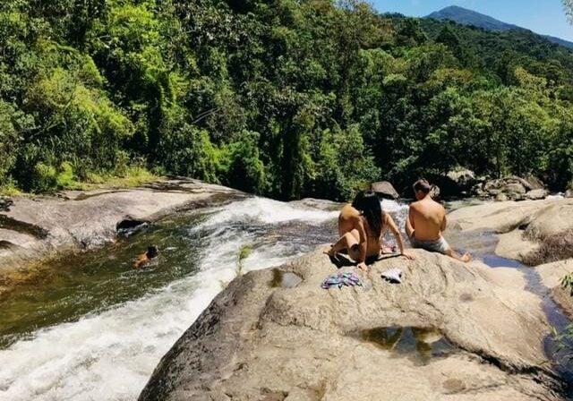 Pessoas sentadas ao lado do rio de uma cachoeira em Visconde de Maua