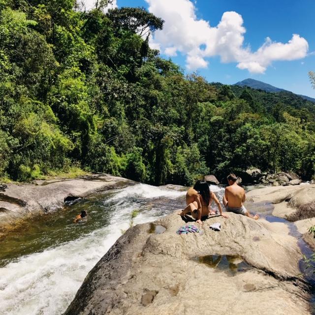Pessoas sentadas ao lado do rio