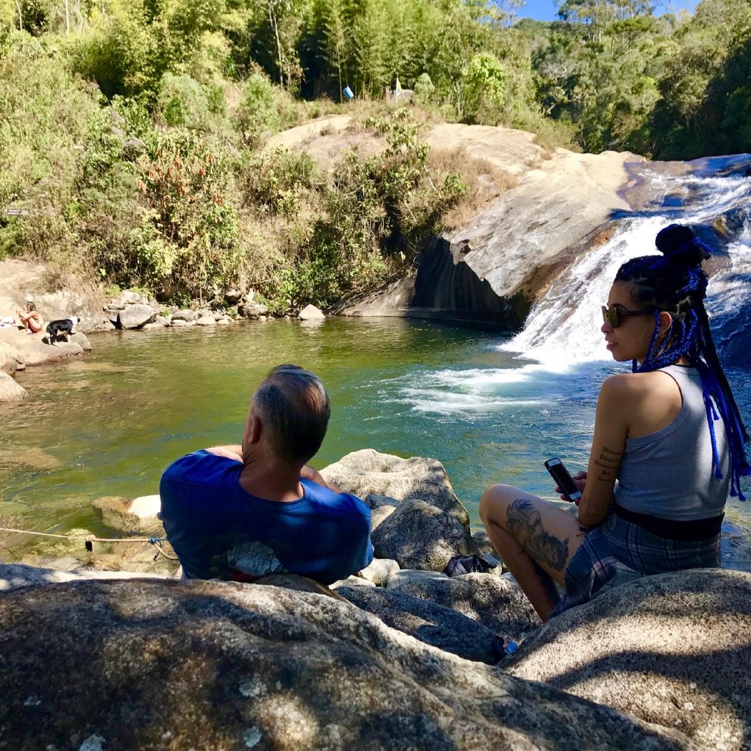 Casal sentado de frente a piscina natural do Escorrega em Visconde de Mauá
