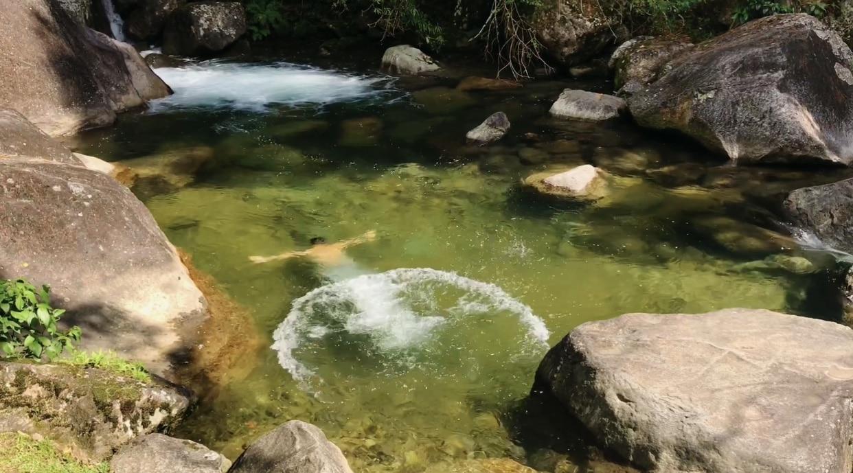 Homem embaixo da água de um rio de águas cristalinas