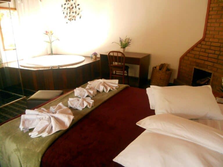 Cama de casal e banheira ao fundo de um chalé em Visconde de Mauá