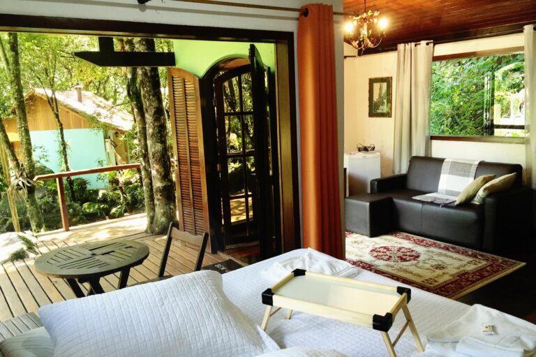 Cama de casal e sala ao fundo do chalé em Visconde de Mauá.