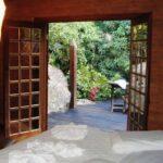Quarto com cama de casal e janela aberta na Pousada Jardim das Águas