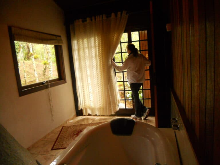 Moca abrindo a cortina da sala com banheira