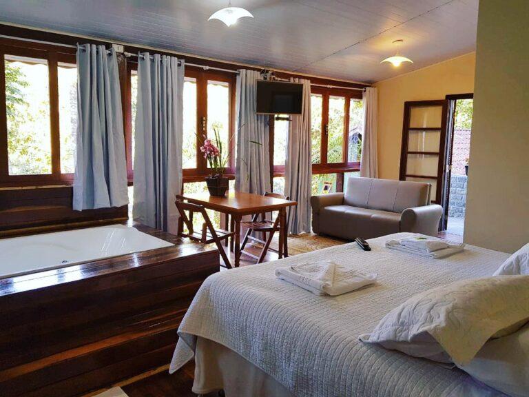 Cama de casal e sala do chalé na vila da Maromba