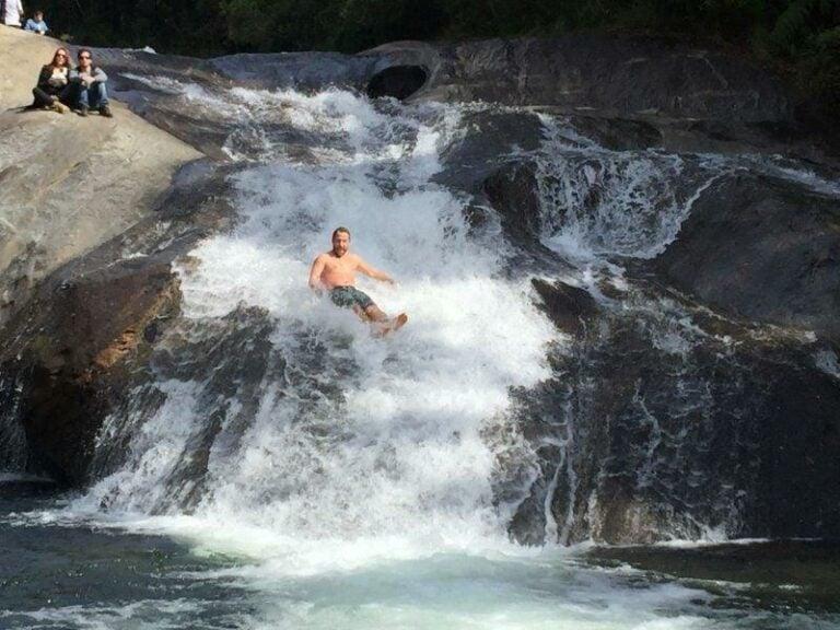 Homem descendo a cachoeira do Escorrega em Visconde de Mauá