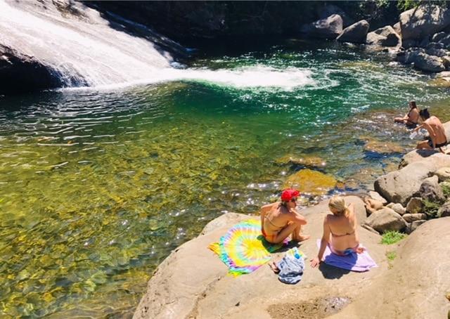 Duas mulhers sentadas na pedra da cachoeira em Visconde de Maua