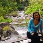 Dona da pousada Jardim das Águas sentada na margem do rio