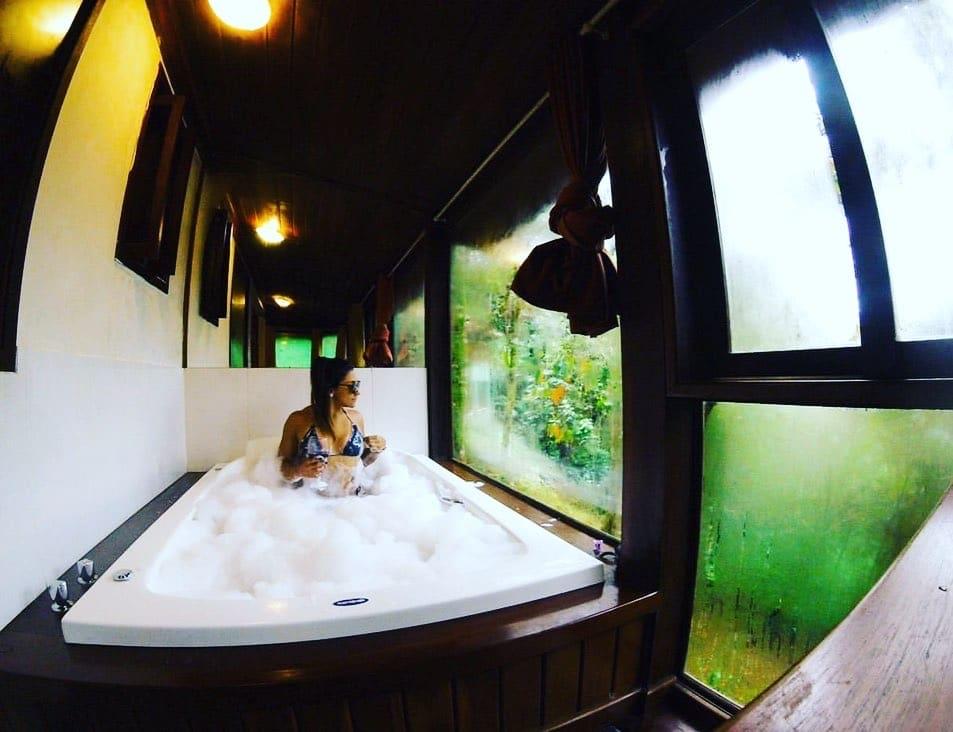Mulher na banheira com vista da mata em Visconde de Mauá