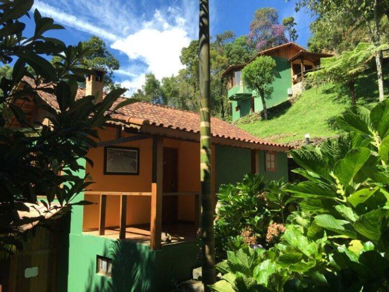 Chalé verde com varanda externa e jardim ao lado