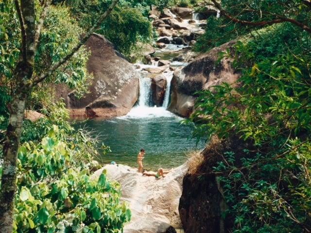 Casal no leito do rio do Poção da Maromba e sua piscina natural