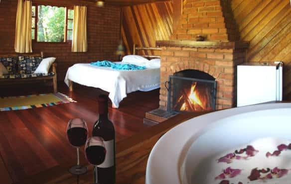 Banheira e cama de casal de um chalé da Pousada das Araucárias