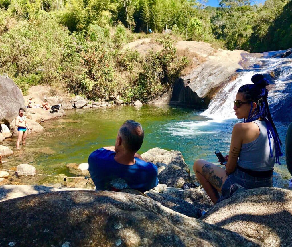Casal tomando sol na pedra ás margens da cachoeira