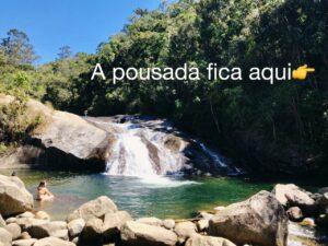 Rio e cachoeira com moça sentada no seu leito de pedras