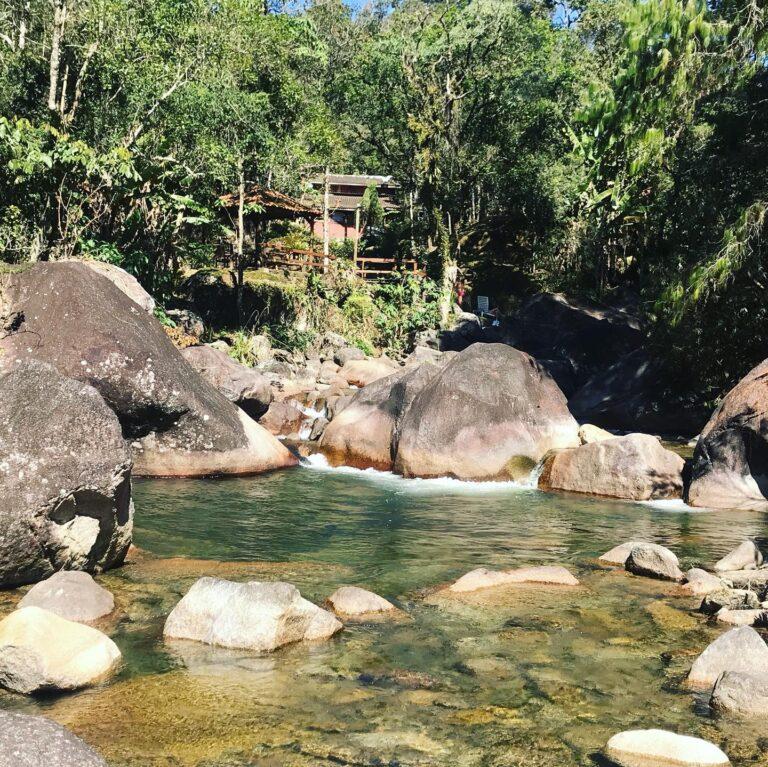 Rio de Visconde de Mauá com pousada ao lado.