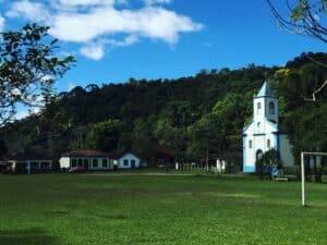 Igreja com campo de futebol na frente da vila de Visconde de Mauá num dia ensolarado
