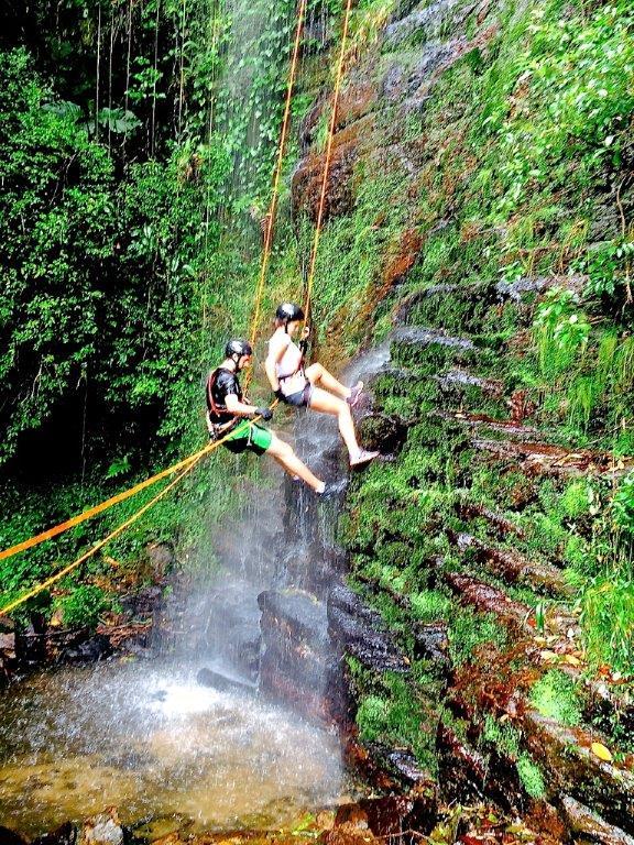 Casal na cachoeira fazendo rapel em Visconde de Maua