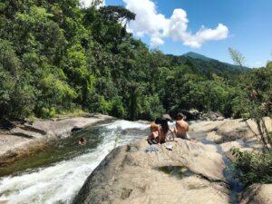 Casal sentado na beira do rio