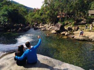 Casal abraçado sentado ao lado da cachoeira