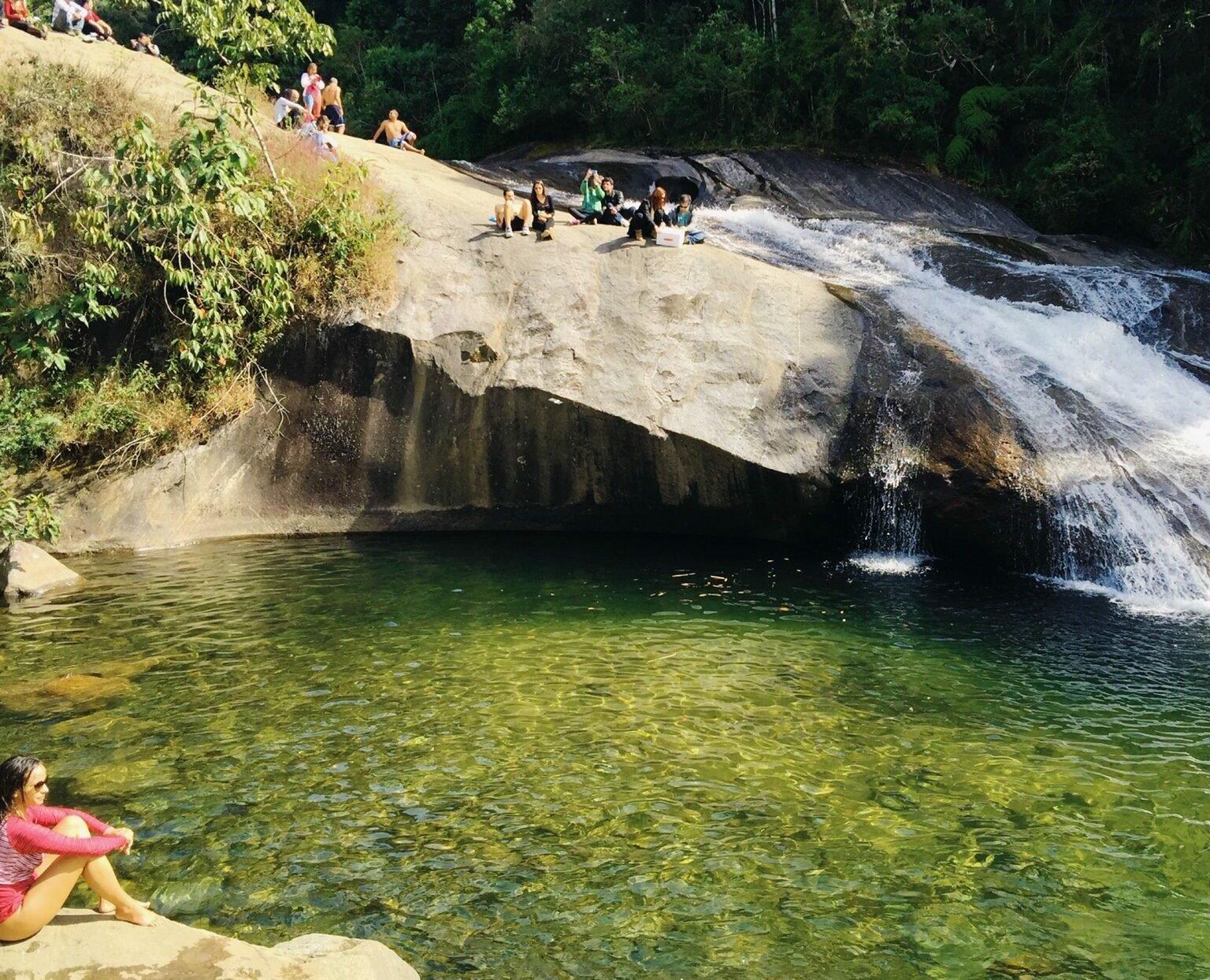 Moça sentada na margem da cachoeira do Escorrega