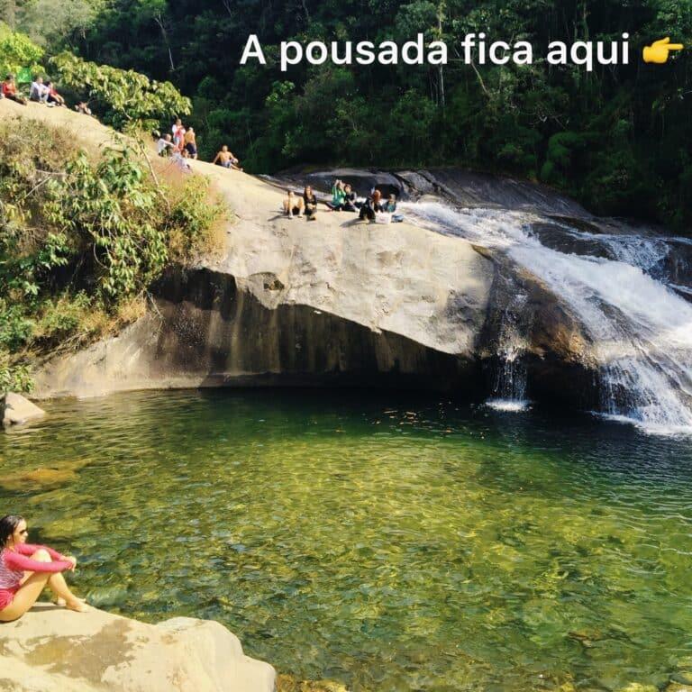 Moça sentada na pedra da cachoeira em Visconde de Mauá