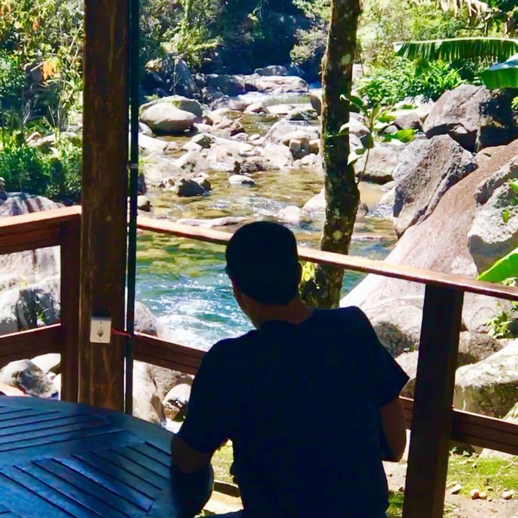 Homem sentado de costas observando o rio da pousada em Visconde de Mauá