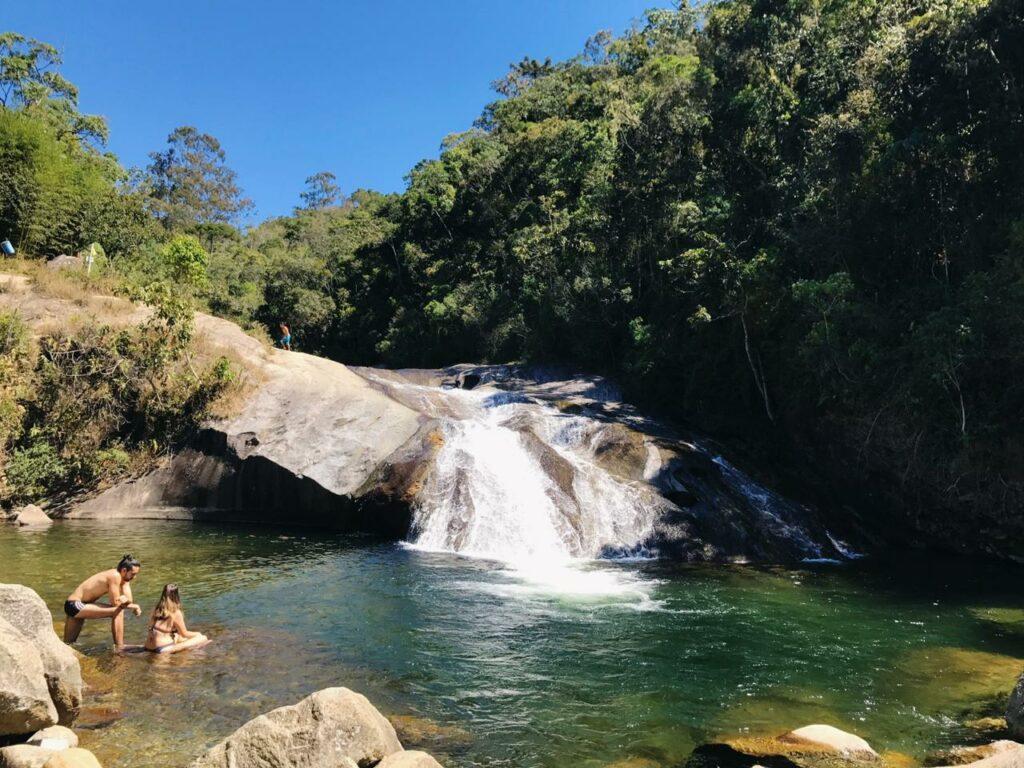 Casal na cachoeira da pousada em Visconde de Mauá