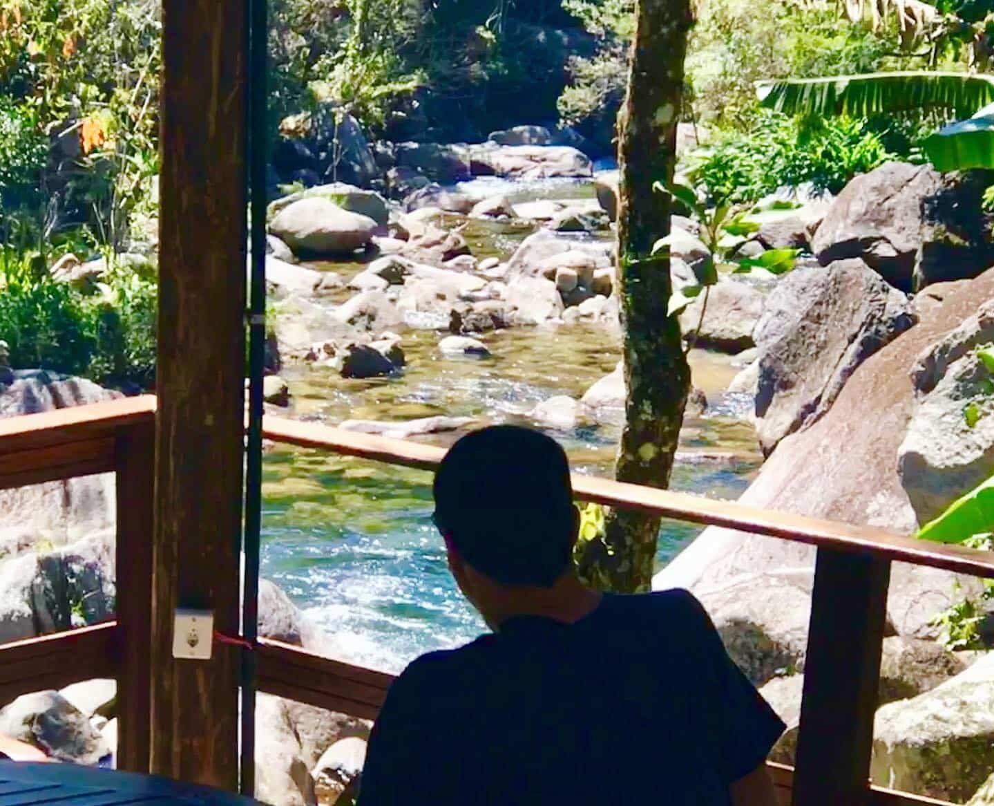 Homem sentado olhando para o rio de Visconde de Mauá