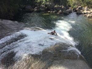 Homem deslizando numa pedra da cachoeira em Visconde de Mauá