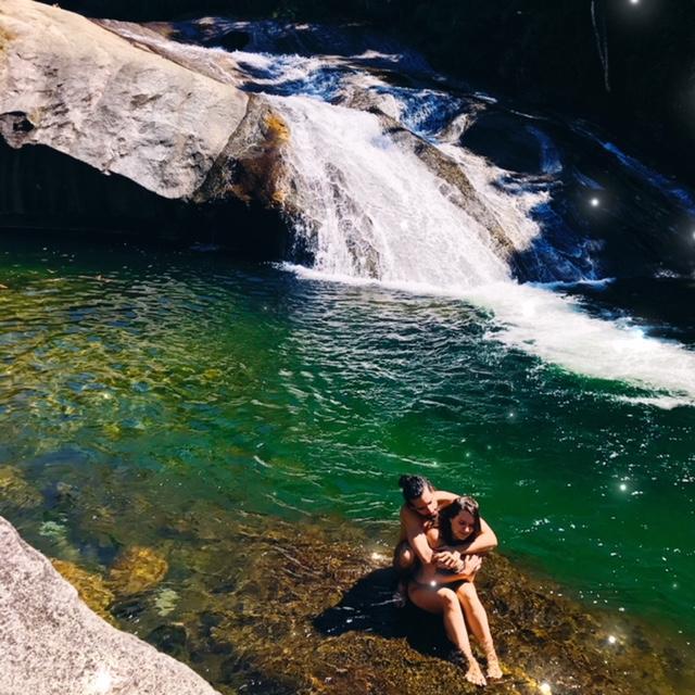 Casal abraçado sentados na pedra no meio da cachoeira