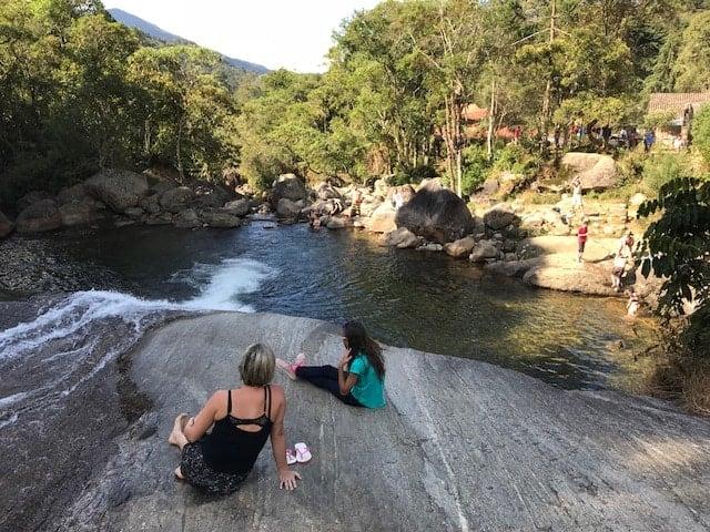 Mãe e filha sentadas na pedra ao lado do rio