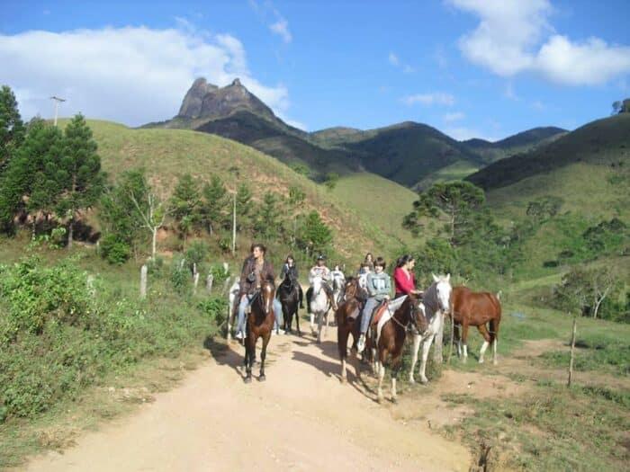 Grupo de pessoas montado à cavalo numa estrada de terra