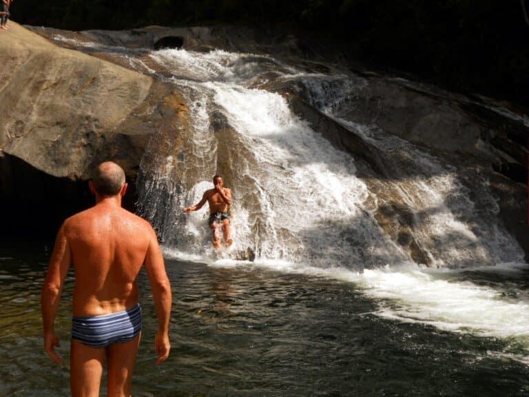 Homem de costas de sunga e uma pessoas deslizando no rio de Visconde de Mauá