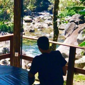 Vulto de homem sentado de costas e de frente a acachoeira em Visconde de Mauá