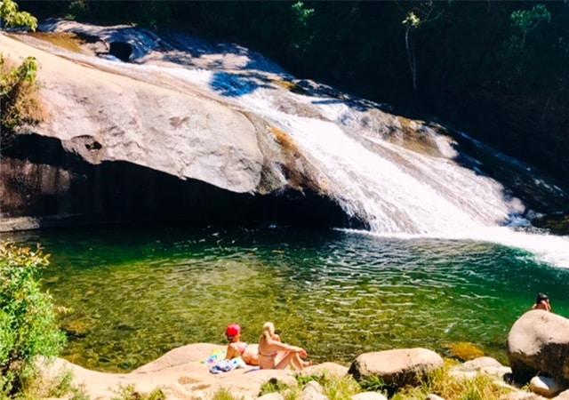 Duas mulheres tomando sol na beira da cachoeira