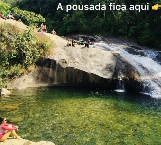 Garota sentada na pedra de um cachoeiras em Visconde de Mauá
