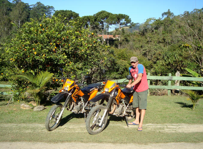 Homem em Visconde de Maua com moto ao lado