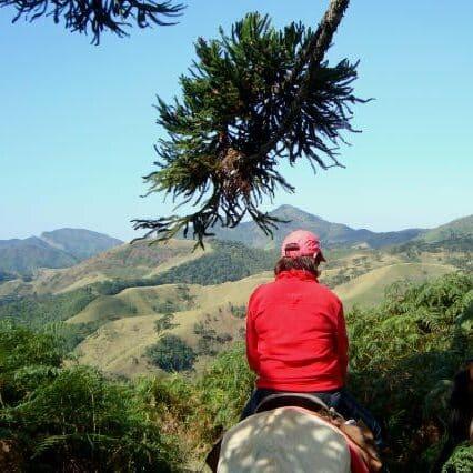 Mulher em cima do cavalo com as escarpas das montanhas de Visconde de Maua ao fundo