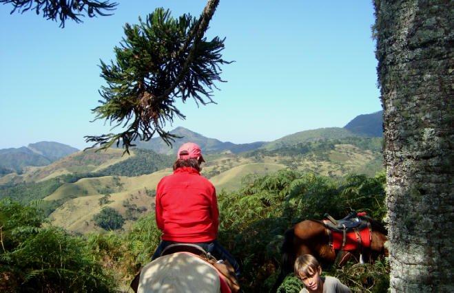 Mujer a caballo con los acantilados de las montañas del Vizconde de Maua al fondo.