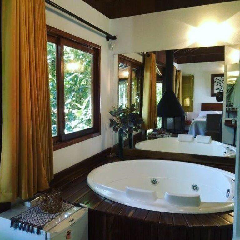 Banheira redonda ao lado da janela na Pousada di Stefano em Visconde de Mauá