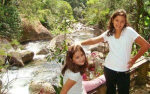Duas crianças felizes brincando na beira do rio em Visconde de