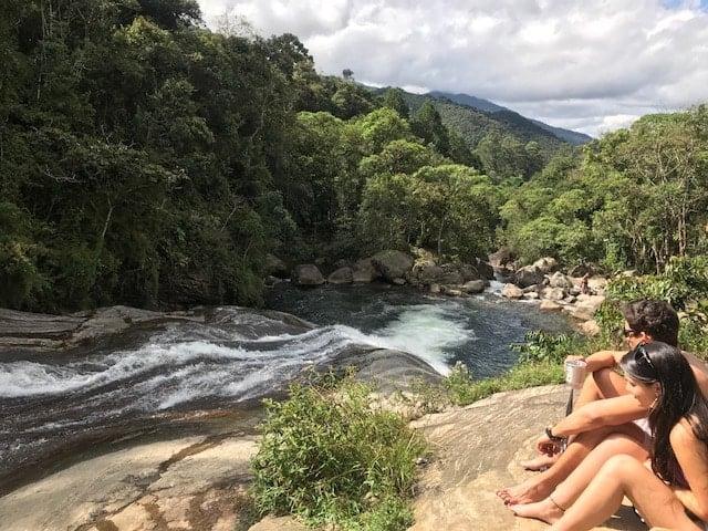 Casal sentado na margem da cachoeira em Visconde de Mauá